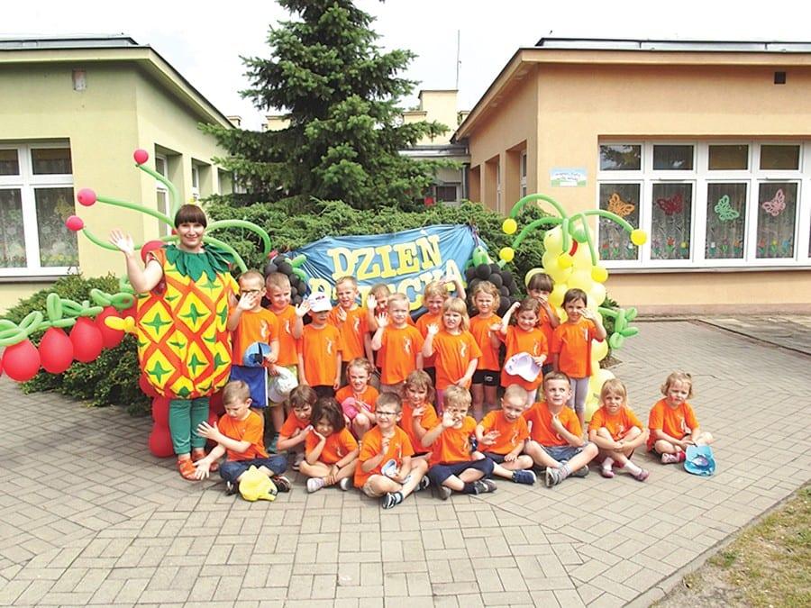 """1 czerwca na dzieci z Miejskiego Przedszkola Integracyjnego we Włodawie czekała niespodzianka - dmuchany plac zabaw i wspaniała zabawa. Ogród przedszkolny zamienił się w owocowo-balonowy sad. Każda grupa zaprezentowała się w pięknych kolorowych koszulkach, które odzwierciedlały owoce. """"Żabki"""" zamieniły się w jabłuszka, """"Słoneczka"""" w banany i cytrynki, """"Tygryski"""" - w ananasy, """"Biedronki"""" - w truskaweczki."""